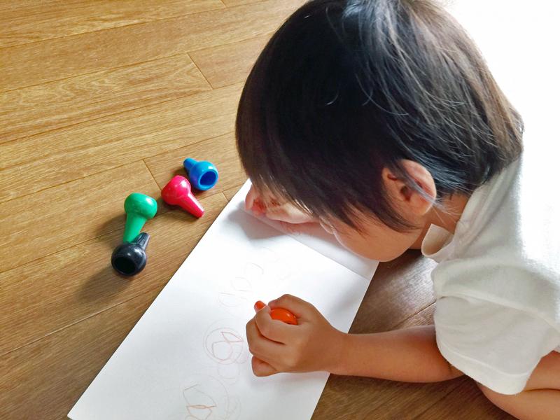子供がうつぶせになって絵を描いている