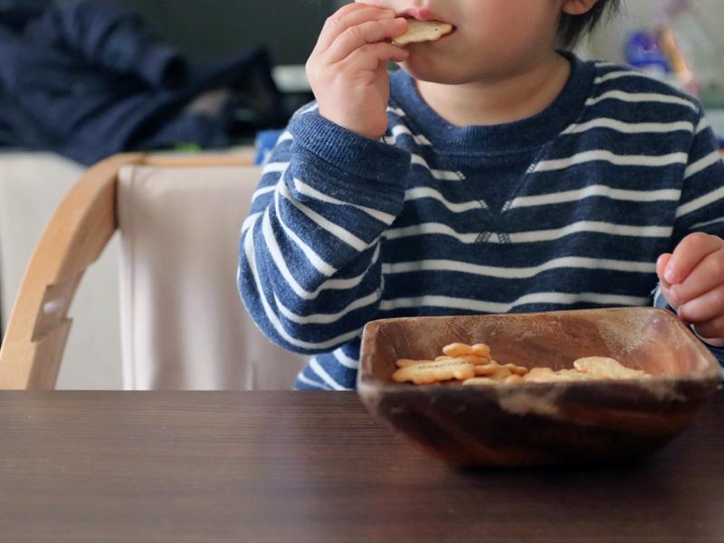 子供が大きな器に入ったビスケットを食べているところ