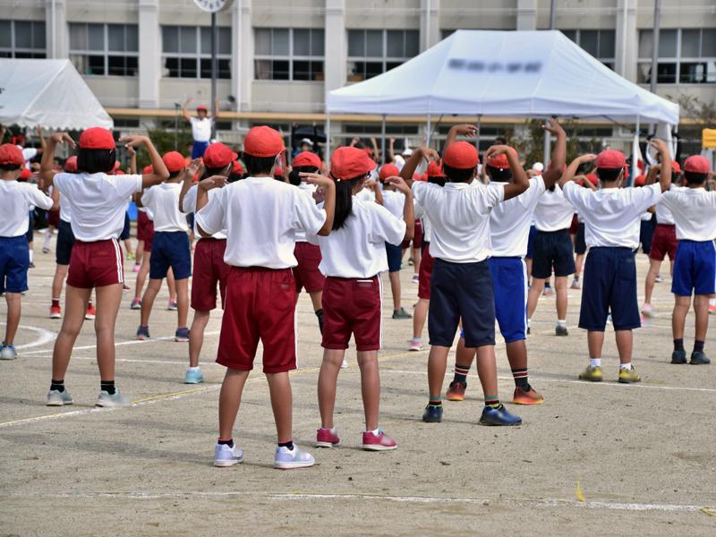 大勢の小学生が体操着を着て、校庭でラジオ体操をしているところ