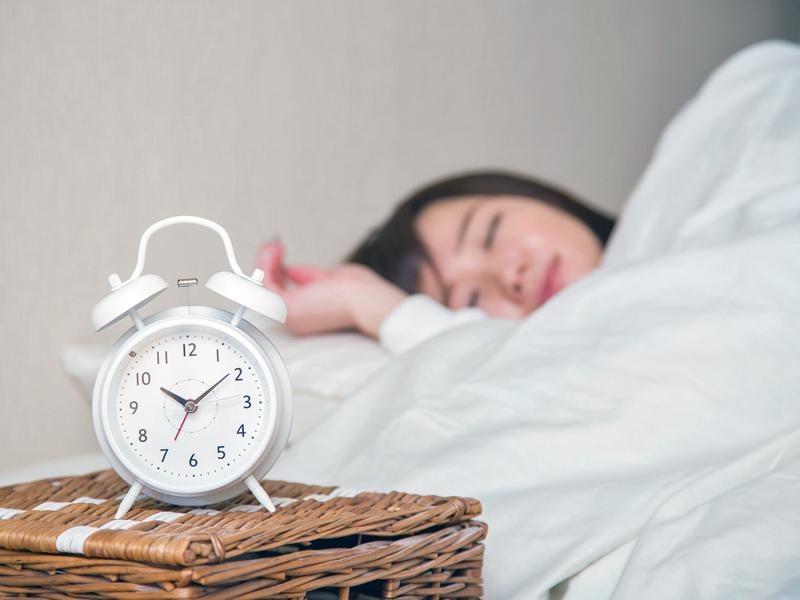 睡眠中の女性の前に目覚まし時計